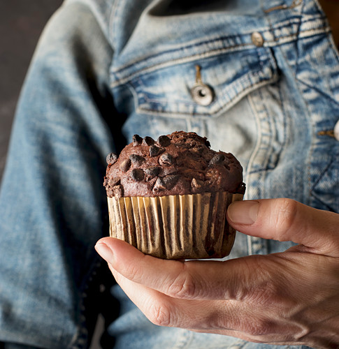Unrecognizable female holding delicious chocolate banana muffin in hand