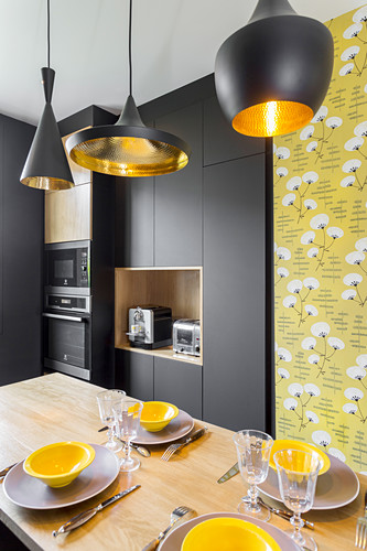 Black and yellow designer kitchen with central dining area