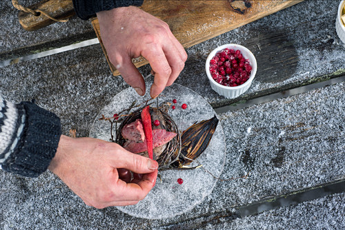A winter barbecue: grilled quail with chilli and berries being plated up (Norway)