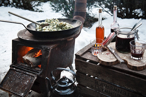 A winter barbecue with pans on a rustic wood-fired oven in the snow