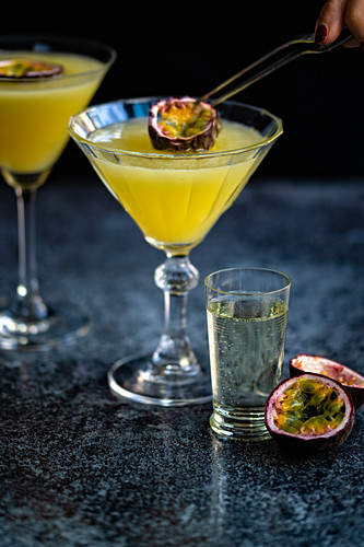 Slice of passion fruit being added to martini glass of Porn Star Martini cocktail