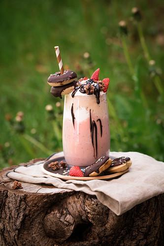 Vegan freakshake made with banana and strawberry ice cream with strawberries and mini doughnuts