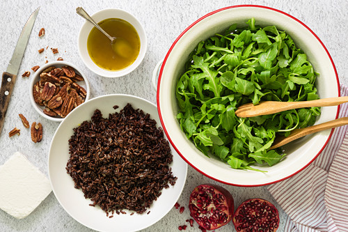 Preparation of ingredients for a rocket, pomegranate and rice salad