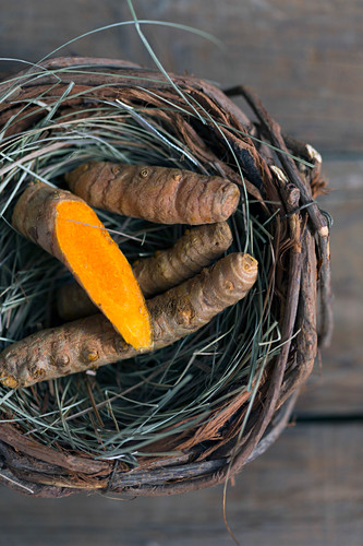 Yummy boiled carrot placed inside small nest on lumber tabletop