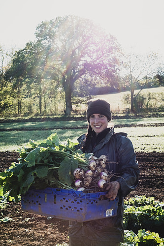 Smiling woman standing in field, holding blue crate with freshly harvested turnips