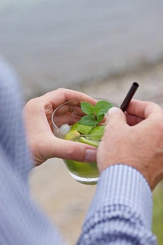 Hands holding a glass of caipirinha