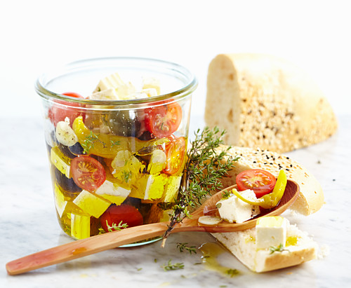 Feta cheese preserved in olive oil with tomatoes, garlic, jalapenos and olives served with unleavened sesame seed bread