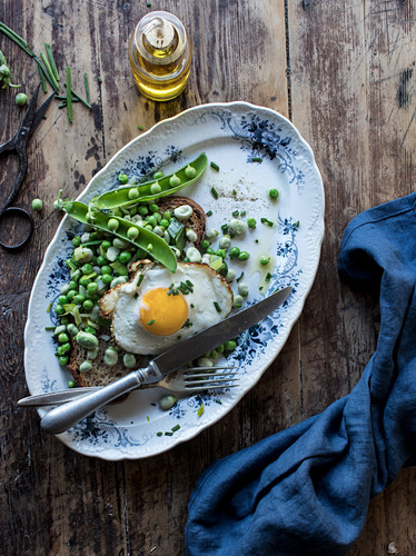 From above of served plate with bread toast with sauteed green peas and fried egg on wooden table