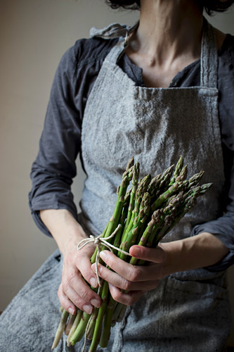 Crop woman in gray textured dress holding tenderly heap of fresh green asparagus stems