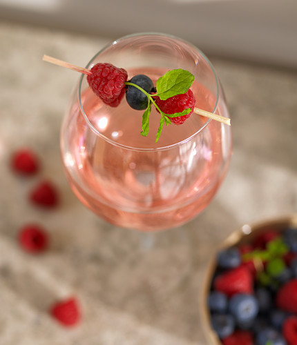 A drink with a berry skewer