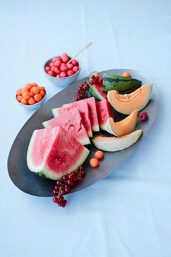 An arrangement of melon with watermelon, cantaloup melon, melon balls and redcurrants