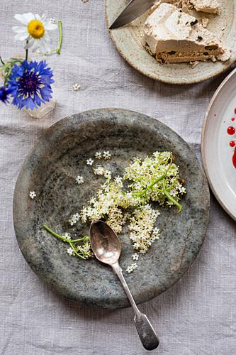 Elderflower in a stone bowl next to halva on a dessert plate