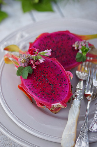Halved dragon fruit with elegant silver cutlery on a plate
