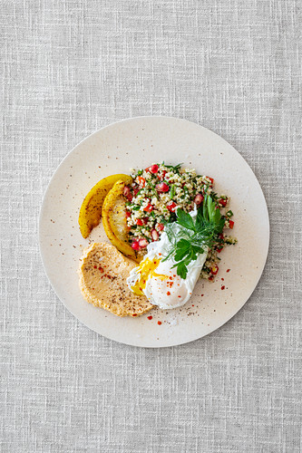 Tabbouleh with pomegranate, grilled salted lemons, hummus and poached egg (Levant cuisine)