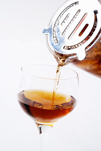 A Manhattan being poured into a glass