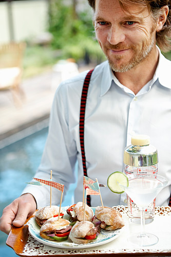 Man with sandwiches and drink on tray