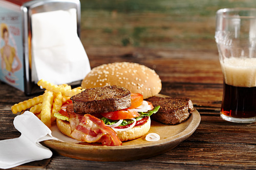 A burger with fried fillet steaks, bacon, ketchup, french fries and cola