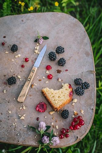 Angebissenes Stück Sommerkuchen mit Himbeeren, Brombeeren und Johannisbeeren