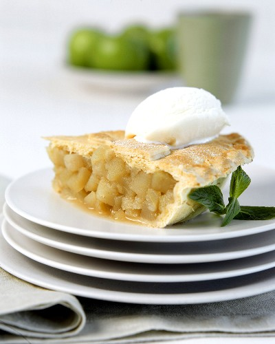 A piece of apple pie with a scoop of ice cream, on plates