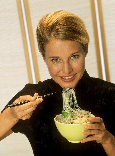 Blond woman eating Asian noodle soup with chopsticks