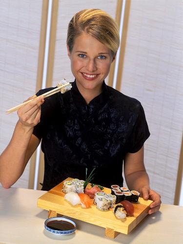 Junge Frau isst Sushi mit Stäbchen