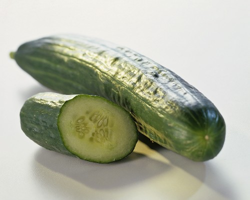 Whole cucumber, a small piece of cucumber beside it