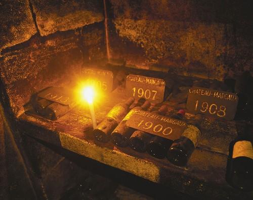 Old Bordeaux bottles (Château Margaux) in wine cellar