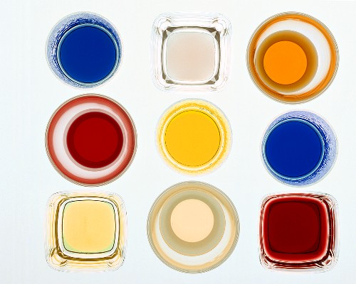 Glasses of liqueurs and sweet syrups photographed from above