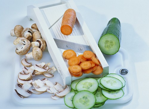 Vegetable slicer with slices of mushrooms, carrots and cucumber