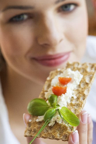 Young woman eating crispbread with herb quark (close-up)