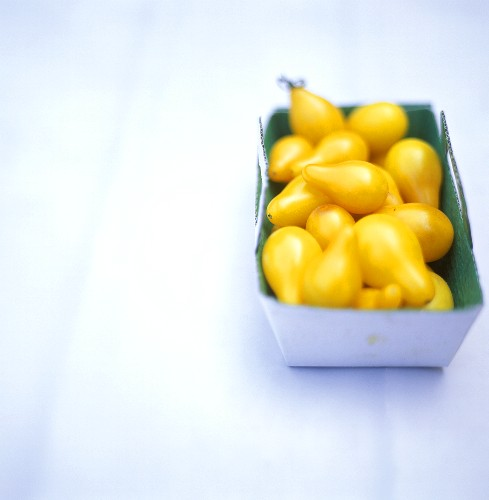 Pear-shaped yellow tomatoes in a cardboard box