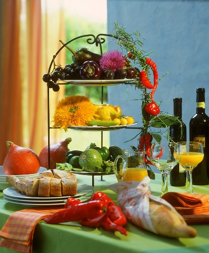 Tiered stand with vegetables and flowers on buffet table