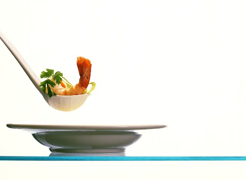Shrimp tail and parsley on soup ladle over plate