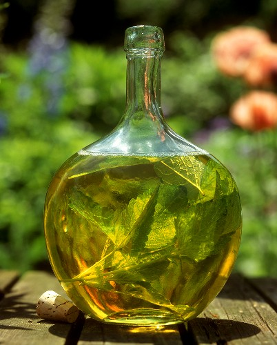 Home-made lemon balm bath oil in decorative glass bottle