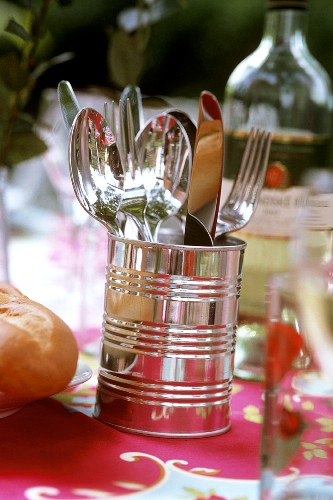 Cutlery in tin on laid table in open air