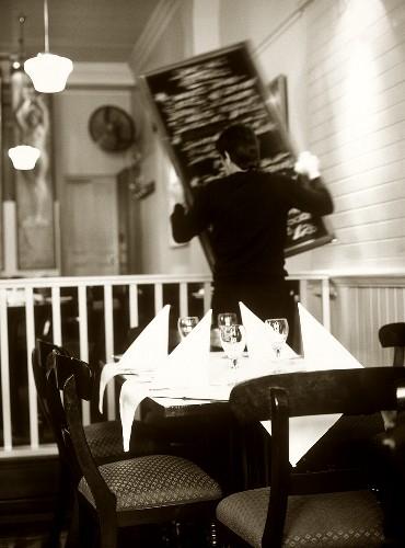 Waiter in a restaurant hanging up menu board