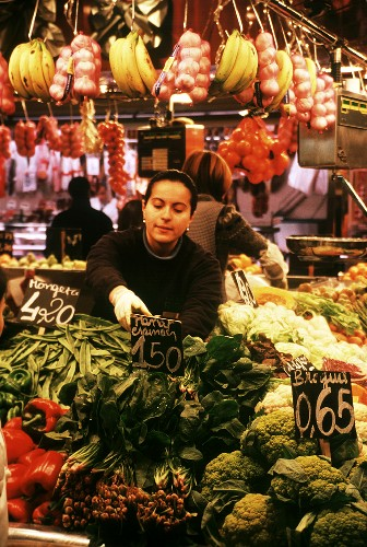 Woman selling vegetables at stall in the Boqueria in Barcelona