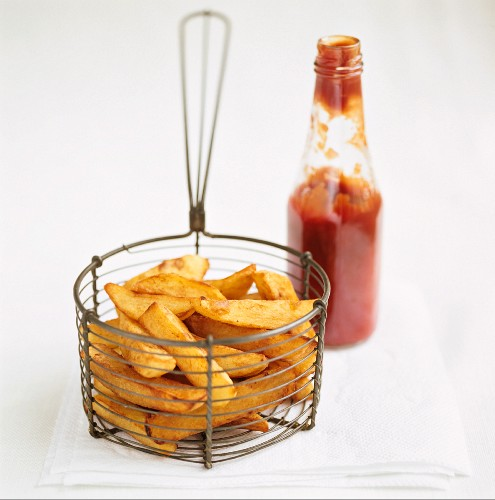 Chips in a basket with a bottle of ketchup