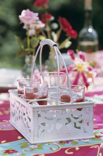Glasses painted with roses standing in a glass carrier
