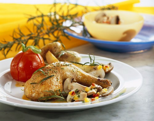 Chicken leg with rosemary, mushroom salad & grilled tomato