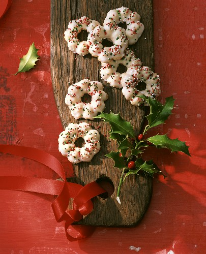 Almond biscuits on a wooden platter with sprig of holly