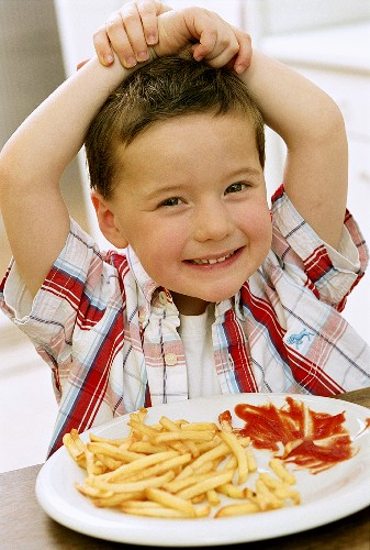 Small boy sitting in front of plate of chips