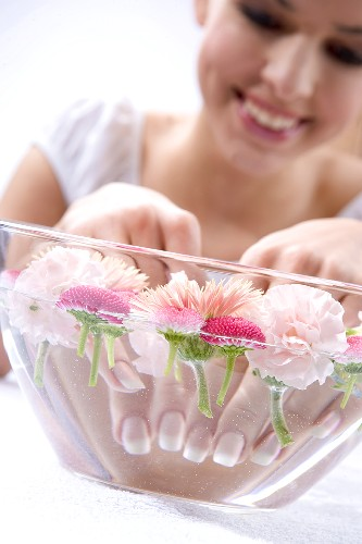 Young woman bathing her hands in a bowl of water with flowers