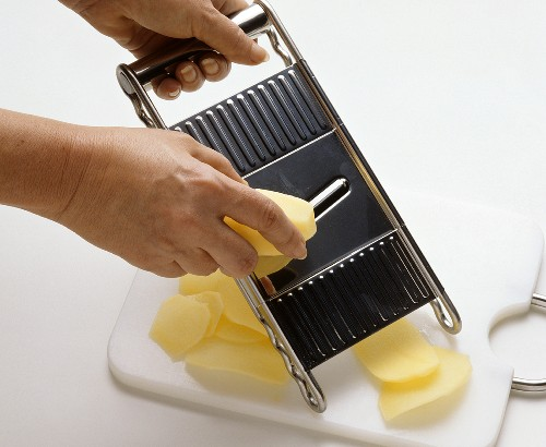 Slicing raw potatoes with cucumber slicer