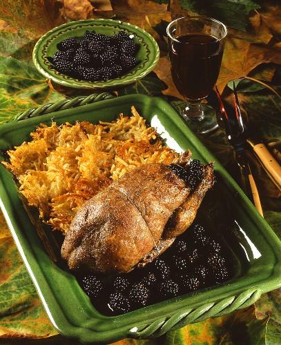 Wild duck with blackberries & potato pancakes; red wine glass