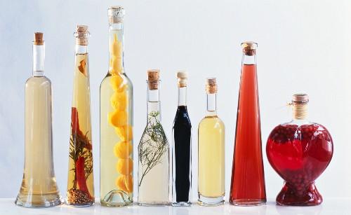 Various types of vinegar in bottles on light background