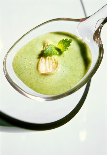 Sorrel soup with oyster mushrooms on a glass spoon