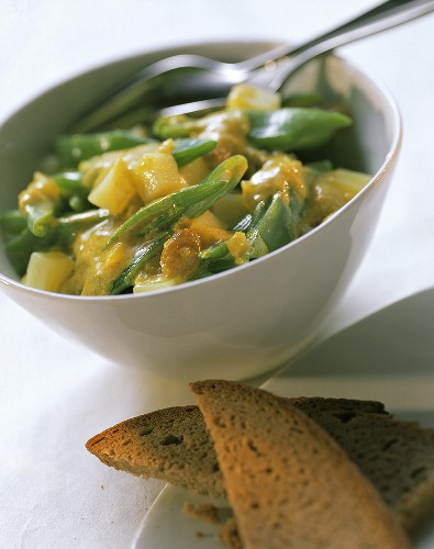 Curried beans with raisins & potatoes in white bowl