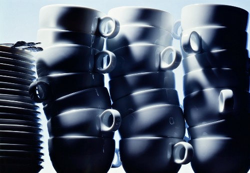 Three piles of cups and a pile of plates with cutlery