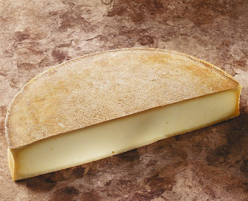 French Abondance cheese on a brown background